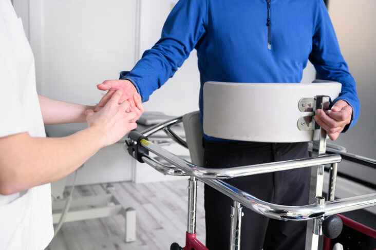 Uma pessoa dando a mão para outra, a qual está com esclerose múltipla